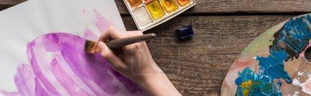 vista recortada del dibujo del artista en cuaderno de bocetos con pinturas de acuarela en la mesa de madera, plano panorámico