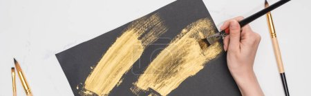 Photo for Partial view of artist drawing brushstrokes with golden paint in black paper on marble surface, panoramic shot - Royalty Free Image