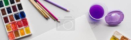 Foto de Vista superior de papel blanco vacío cerca de lápices de colores y pinturas de acuarela en la superficie blanca de mármol, tiro panorámico - Imagen libre de derechos