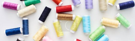 Foto de Foto panorámica de hilos brillantes y coloridos sobre fondo blanco - Imagen libre de derechos