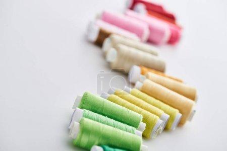 Foto de Enfoque selectivo de hilos brillantes y coloridos sobre fondo blanco - Imagen libre de derechos