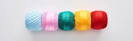 Photo pour Coup panoramique des boules lumineuses et colorées de fil de tricot sur le fond blanc - image libre de droit