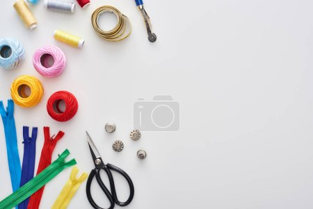 Foto de Top view of zippers, scissors, thimbles, threads, knitting yarn balls, bobbins, tracing wheel, measuring tape on white background - Imagen libre de derechos