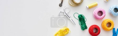 Photo for Panoramic shot of zipper, scissors, threads, knitting yarn balls, tracing wheel, measuring tape on white background - Royalty Free Image