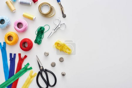 Photo for Top view of zippers, scissors, thimbles, threads, knitting yarn balls, bobbins, tracing wheel, measuring tape on white background - Royalty Free Image