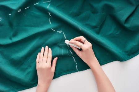 Foto de Top view of seamstress drawing on colorful fabric with chalk on white background - Imagen libre de derechos