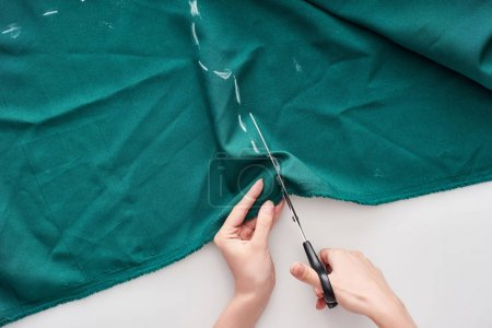 Photo for Top view of seamstress cutting colorful fabric with scissors on white background - Royalty Free Image