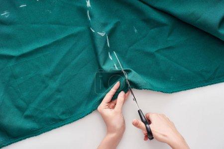 Photo pour Vue supérieure de la couturière coupant le tissu coloré avec des ciseaux sur le fond blanc - image libre de droit