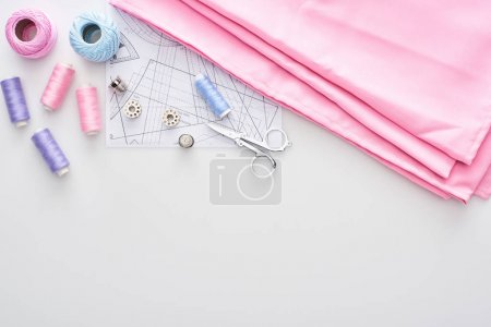 Photo for Top view of fabric, knitting yarn balls, sewing pattern, scissors, thimbles, bobbins and threads on white background - Royalty Free Image