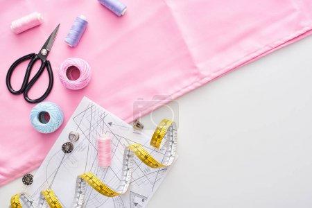 Photo pour Vue du dessus du tissu, boules de fil de tricot, modèle de couture, ciseaux, thimbles, bobines, ruban à mesurer et fils sur le fond blanc - image libre de droit