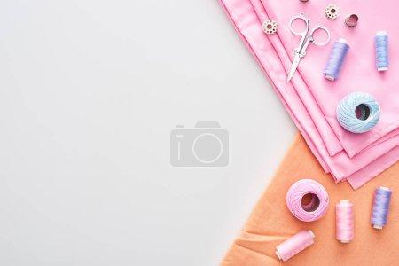 Photo pour Vue du dessus du tissu, boules de fil de tricot, ciseaux, dé à l'etoyble, bobines et fils sur fond blanc - image libre de droit