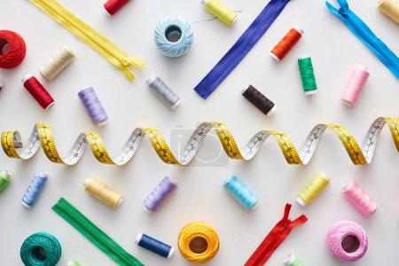 Foto de Top view of measuring tape, colorful threads and zippers on white background - Imagen libre de derechos