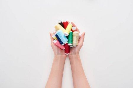 Foto de Vista recortada de la mujer sosteniendo hilos brillantes y coloridos sobre fondo blanco - Imagen libre de derechos