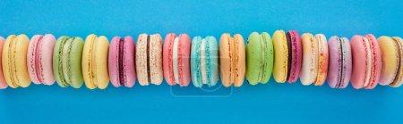 Foto de Foto panorámica de deliciosos macarrones franceses multicolores en fila sobre fondo brillante azul - Imagen libre de derechos