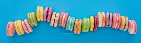 Photo for Top view of multicolored delicious French macaroons in curved line on blue bright background, panoramic shot - Royalty Free Image