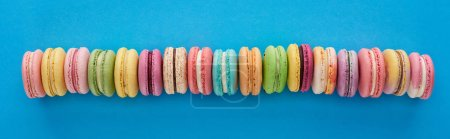 Photo for Top view of multicolored delicious French macaroons in row on blue bright background, panoramic shot - Royalty Free Image