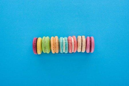 Photo pour Vue du haut des macarons Français délicieux multicolores en ligne sur le fond lumineux bleu - image libre de droit