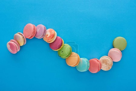 Photo for Top view of multicolored delicious French macaroons in curved line on blue bright background with copy space - Royalty Free Image