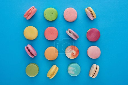 Photo for Flat lay with multicolored delicious French macaroons on blue bright background - Royalty Free Image