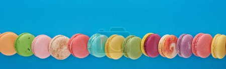 Photo for Line of multicolored delicious French macaroons on blue bright background with copy space, panoramic shot - Royalty Free Image