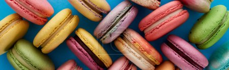 Photo for Top view of colorful assorted French macaroons on blue bright background, panoramic shot - Royalty Free Image