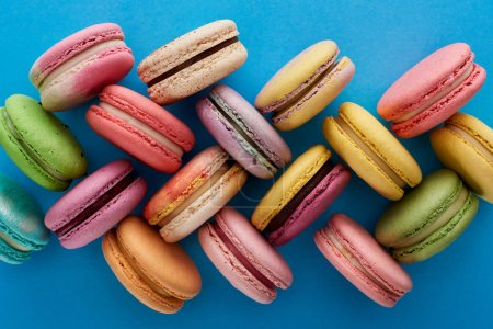 Photo for Top view of assorted delicious French macaroons on blue bright background - Royalty Free Image