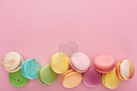 Draufsicht auf bunte köstliche französische Makronen auf rosa Hintergrund mit Kopierraum