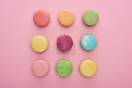 Photo for Flat lay with delicious French macaroons on pink background - Royalty Free Image