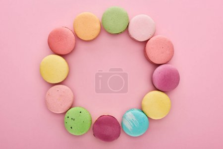 Photo for Frame of multicolored delicious French macaroons with copy space on pink background - Royalty Free Image