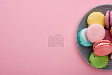 Photo for Plate with multicolored delicious French macaroons on pink background with copy space - Royalty Free Image