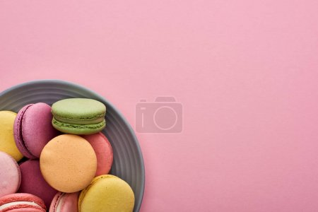 Photo for Close up view of plate with multicolored delicious French macaroons on pink background - Royalty Free Image