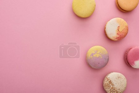 Photo for Top view of multicolored delicious French macaroons on pink background - Royalty Free Image