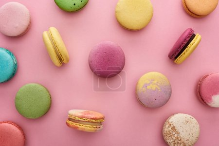 Photo for Pattern of multicolored delicious French macaroons scattered on pink background - Royalty Free Image