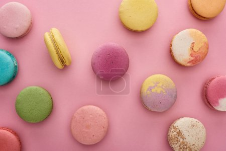 Photo for Pattern of multicolored tasty French macaroons scattered on pink background - Royalty Free Image