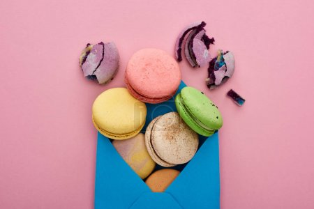 Photo for Top view of multicolored delicious French macaroons in blue postal envelope on pink background - Royalty Free Image