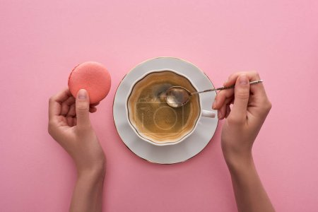 Photo for Partial view of woman holding spoon near coffee in cup and delicious French macaroon on pink background - Royalty Free Image