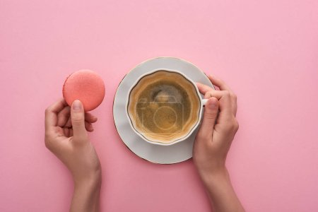 Photo for Partial view of woman drinking coffee with delicious French macaroon on pink background - Royalty Free Image