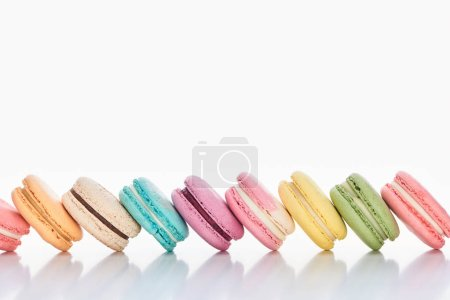 Photo for Row of delicious colorful French macaroons of different flavors on white background with copy space - Royalty Free Image