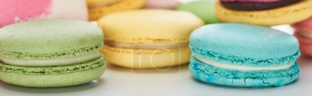 Photo for Close up view of sweet colorful French macaroons of different flavors on white background, panoramic shot - Royalty Free Image