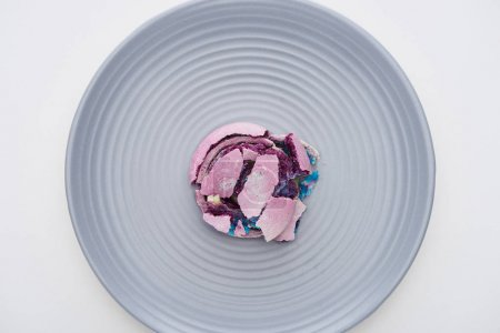 Photo for Top view of delicious purple smashed French macaroon on plate isolated on white - Royalty Free Image