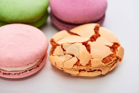 Photo for Close up view of sweet colorful French macaroons of different flavors with smashed one on white background - Royalty Free Image