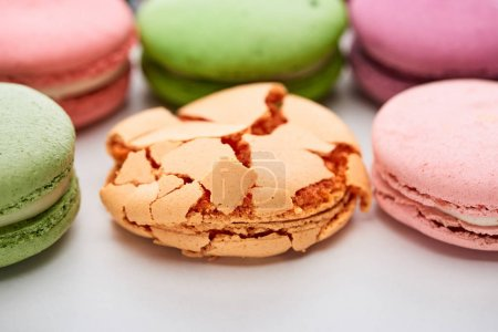 Photo for Close up view of colorful French macaroons of different flavors with smashed one on white background - Royalty Free Image