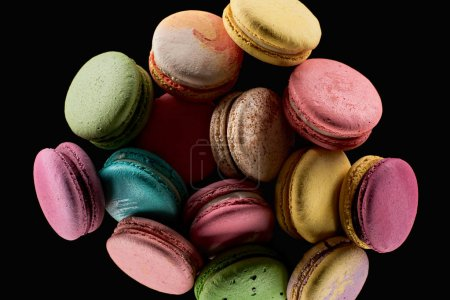 Photo for Pile of delicious colorful French macaroons of different flavors isolated on black - Royalty Free Image