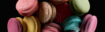 Photo for Stack of delicious colorful French macaroons of different flavors isolated on black, panoramic shot - Royalty Free Image