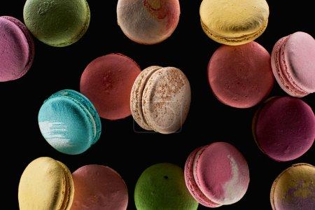 Foto de Vista superior de deliciosos y coloridos macarrones franceses de diferentes sabores aislados en negro - Imagen libre de derechos