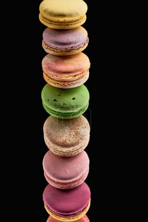 Photo for Row of delicious colorful French macaroons of different flavors isolated on black - Royalty Free Image