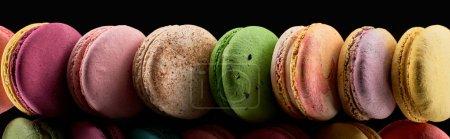 Foto de Fila de coloridos macarrones franceses de diferentes sabores aislados en negro, tiro panorámico - Imagen libre de derechos