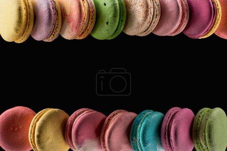 Photo pour Des rangées de délicieux macarons colorés de Français de différentes saveurs isolés sur le noir avec l'espace de copie - image libre de droit