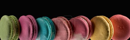 Photo for Row of tasty colorful French macaroons of different flavors isolated on black, panoramic shot - Royalty Free Image
