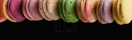 Photo for Row of tasty colorful French macaroons of different flavors isolated on black with copy space, panoramic shot - Royalty Free Image